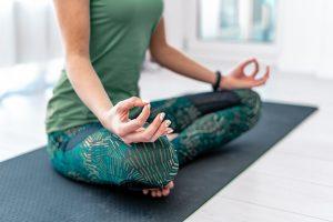 Frau in Mediation Schneidersitz, Frau auf Matte meditiert